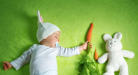 Baby in rabbit hat eating carrot