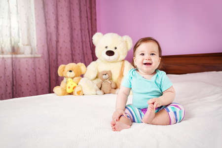 Cute smiling little baby girl sitting on the bed with soft toys Stock Photo