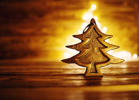 Fir tree toy on wooden background with christmas lights. Imagens