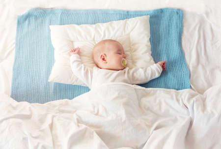 Bambino che dorme sulla coperta blu Archivio Fotografico - 93572049
