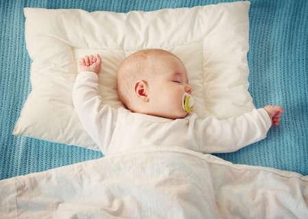 Bambino che dorme sulla coperta blu Archivio Fotografico - 93410143