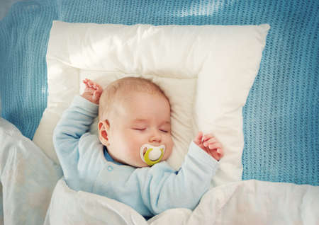 Bambino che dorme sulla coperta blu Archivio Fotografico - 93411693