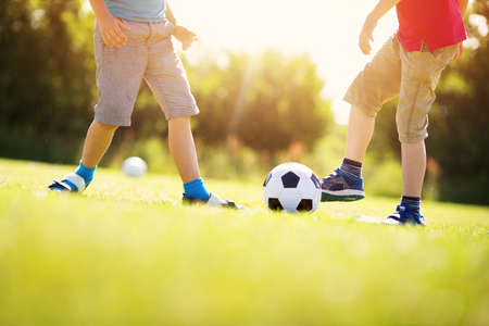 Boys playing football on the field with gates Stockfoto
