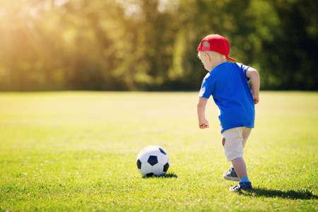 Petit garçon jouant au football sur le terrain avec des portes Banque d'images - 94276814