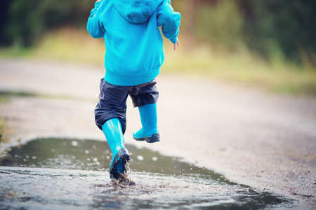 Child walking in wellies in puddle on rainy weather Фото со стока