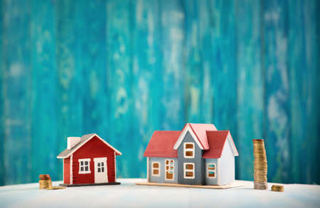 Red house on wooden background with banknotes