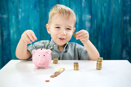 three years old child sitting st the table with money and a piggybank Stok Fotoğraf