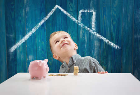 three years old child sitting st the table with money and a piggybank Stock Photo