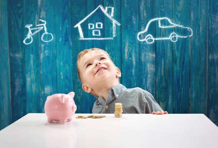 お金と貯金箱でテーブルに座っている3歳の子供
