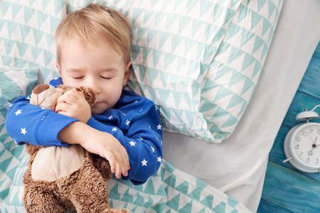 three years old child sleeping in bed with alarm clock