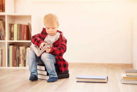 Three years old child sitting among books at home