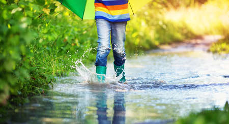 Child walking in wellies in puddle on rainy weather Imagens - 98132561