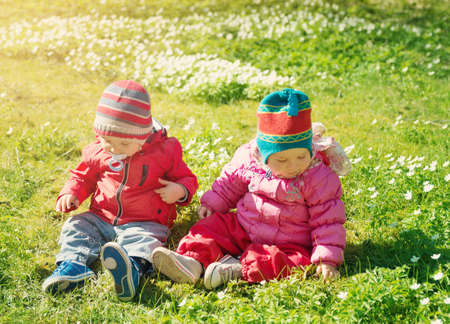 Little boy and girl in hats sitting on the field with soft toys in summer Stock Photo - 98375136