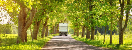 Truck moving on alley in summer