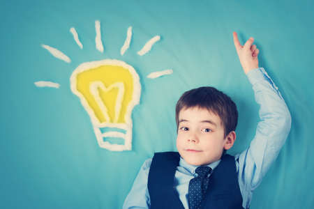 seven years old boy and a bulb near. Child with an idea Stockfoto