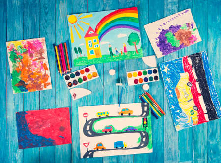 child drawings with draw accessories on blue wooden background