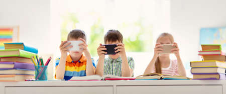 Children sitting in the room with smart phones