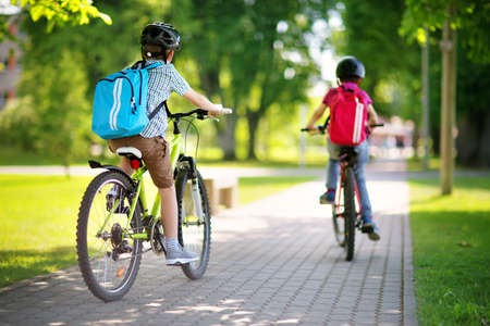 Children with rucksacks riding on bikes in the park near school Foto de archivo