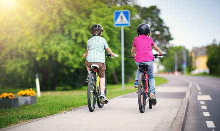 Children with rucksacks riding on bikes in the park near school Archivio Fotografico
