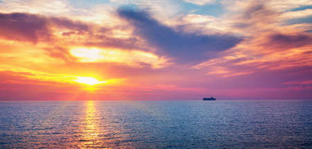 dramatic sunset at the sea with ferry on the background Stok Fotoğraf