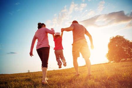 niña con madre y padre tomados de la mano en la naturaleza Foto de archivo