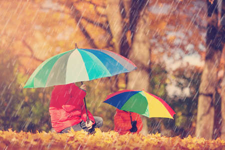 children with umbrellas in beautiful autumnal day