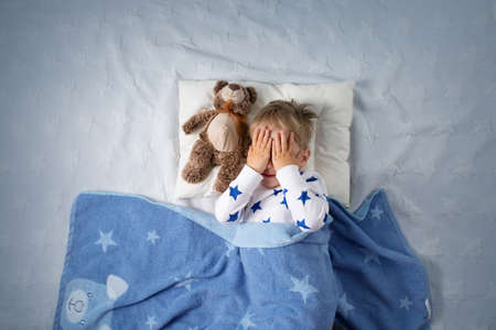 Three years old child crying in bed. Sad boy on pillow in bedroom Stock Photo