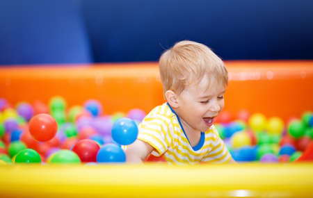Little boy playing on playroom with ballpit