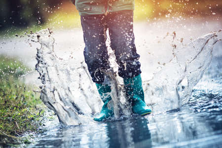 Child walking in wellies in puddle on rainy weather. Boy under rain in summer