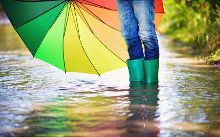 Kind, das in Gummistiefeln in der Pfütze auf Regenwetter geht. Junge, der bunten Regenschirm unter Regen im Sommer hält