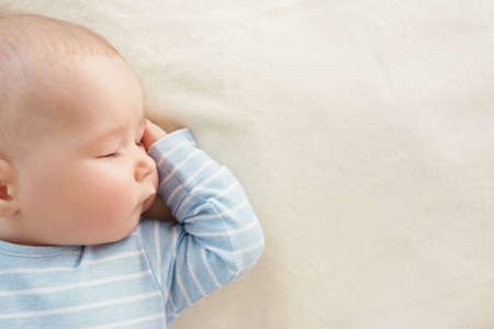 Baby sleeping covered with soft white blanket Stock Photo