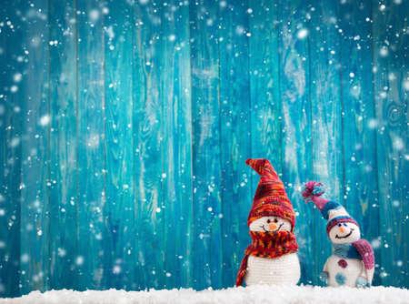 kleine Schneemänner auf weichem Schnee auf blauem Hintergrund