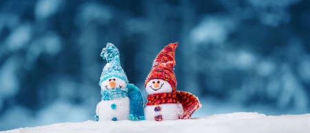 little knitted snowmans on soft snow on blue background Stock Photo