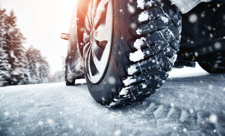 Closeup of car tires in winter on the road Stock Photo