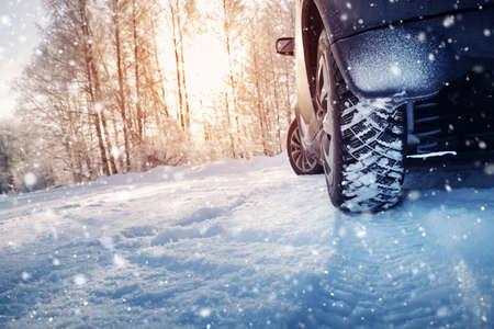 Neumáticos de coche en carretera de invierno cubierto de nieve
