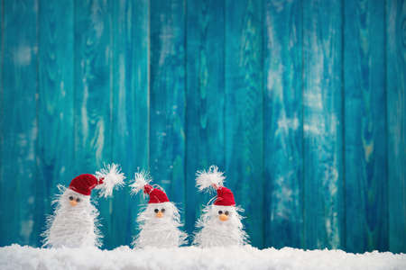 little snowmans on soft snow on blue background
