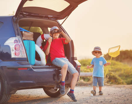 child sitting in car filled with traveling accessories