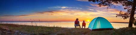 Familie rusten met tent in de natuur bij zonsondergang