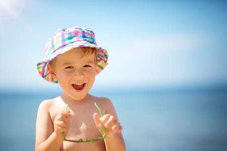 kleine jongen glimlachend op het strand in hoed met zonnebril