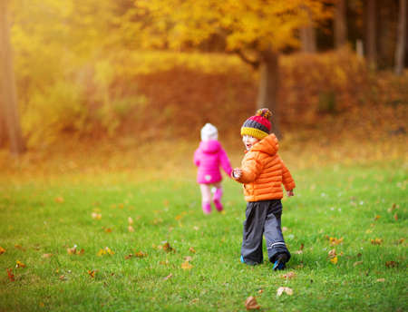 children throwing leaves in beautiful autumnal day