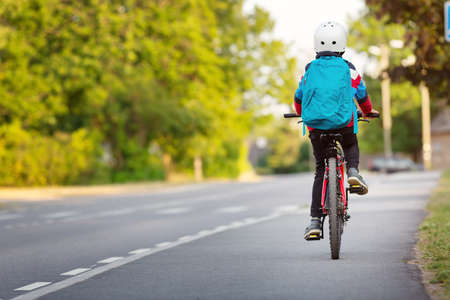 Child with rucksack riding on bike in the park near school