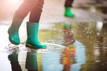 Kind, das in Gummistiefeln in der Pfütze auf Regenwetter geht