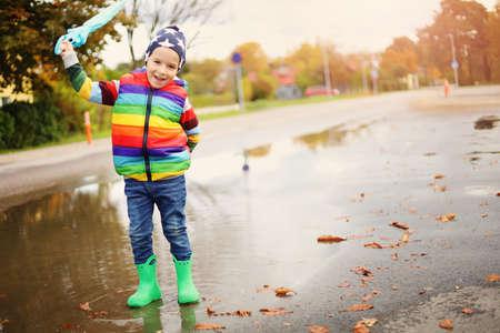 Niño caminando en botas de agua en charco en tiempo lluvioso Foto de archivo