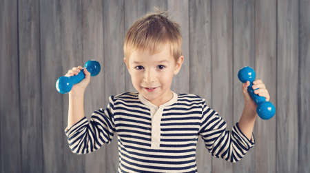 Child holding dumbbells indoors on wooden background. Zdjęcie Seryjne