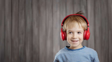 little boy on wooden background with red headphones Stok Fotoğraf