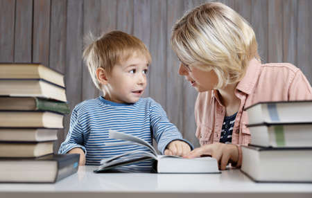 five years old child reading a book at home with mother