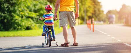 아스팔트 도로에서 아버지와 함께 헬멧을 쓴 자전거를 탄 아이