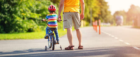 a child on a bicycle in helmet with father on asphalt road