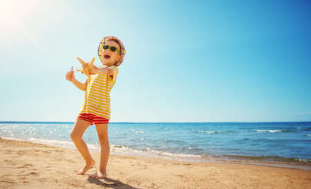 little boy smiling at the beach in hat with sunglasses Archivio Fotografico - 137894002