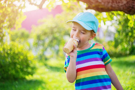 Happy child eating ice cream outdoors in summer